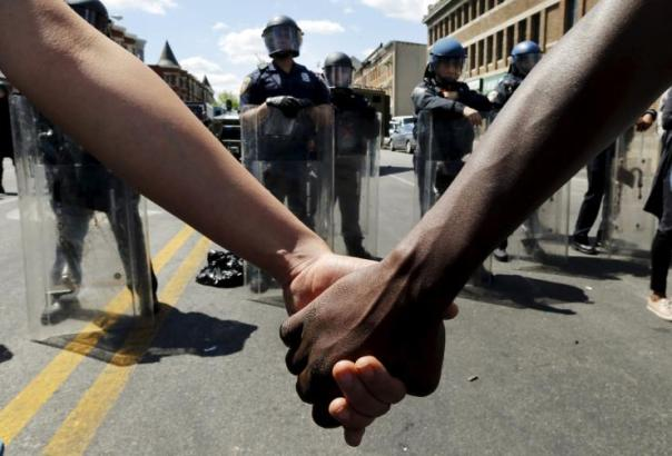Members of the community hold hands in front of police officers in riot gear in Baltimore, April 28, 2015. Reuters/Jim Bourg